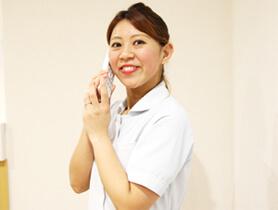 電話を持つ受付の女性の写真